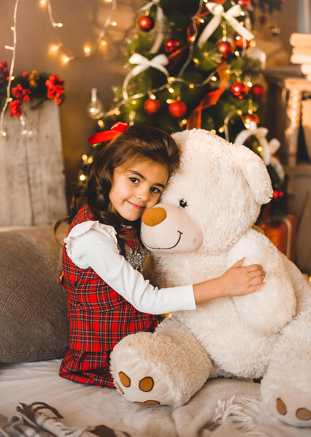 A little girl hugging a big teddy