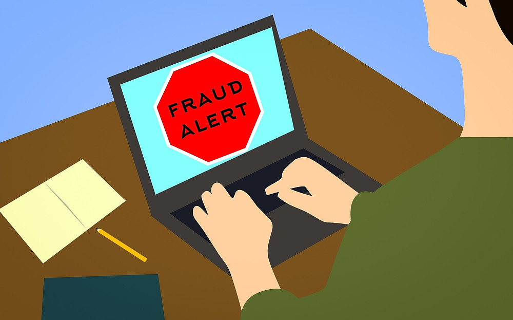 a man looked at a laptop saying 'Fraud Alert'