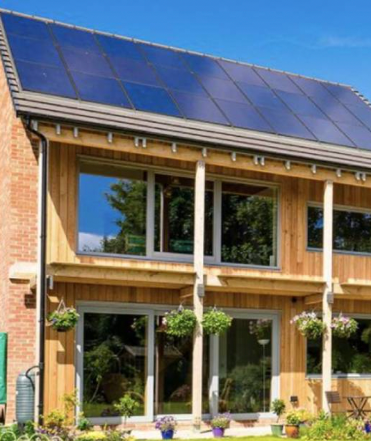 Passivhaus with light wooden panelling covering most of the walls, with red bricks visible at the side of the house. It has large windows and solar panels that cover the roof.