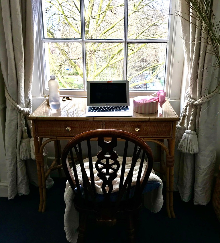 A desk where someone is working in front of a window