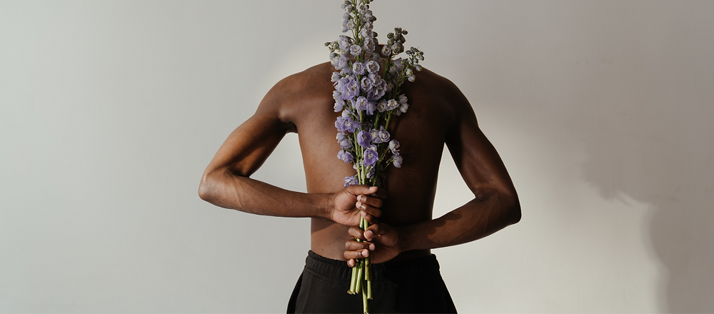 gay man with flowers showing off his body image