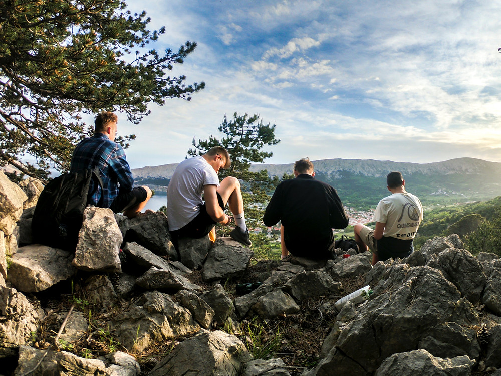 Group of staff members on a corporate wellness retreat hiking up a rocky mountain