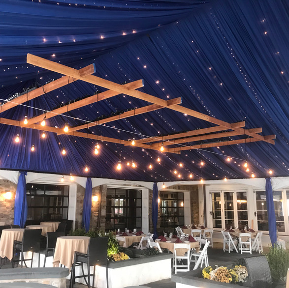Sheer navy tent liner with leg coverings, drape imbued with B-light and market lighting  also featured..Floating pergola with hanging globe lights