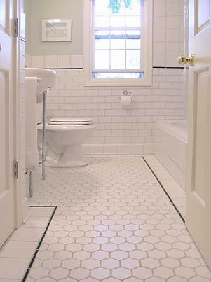 This bathroom design features old world charm using white ceramic tile in various sizes which adds to the charm. The tile design features hexagon floor tile,3x6 subway tile for the walls and 6x6 tile above the subway tile with black pencil liner tile.Wheat Ridge tile installers Action Shower Pan.Com