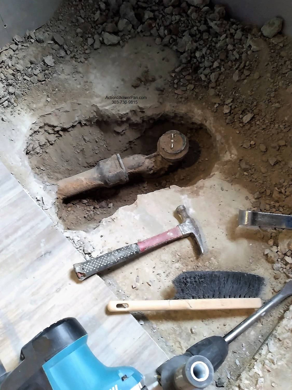 The old cast iron p-trap is removed so that the new Schluter-Kerdi drain can be installed. Because the shower sits on a concrete slab we need to break out the concrete to below grade.