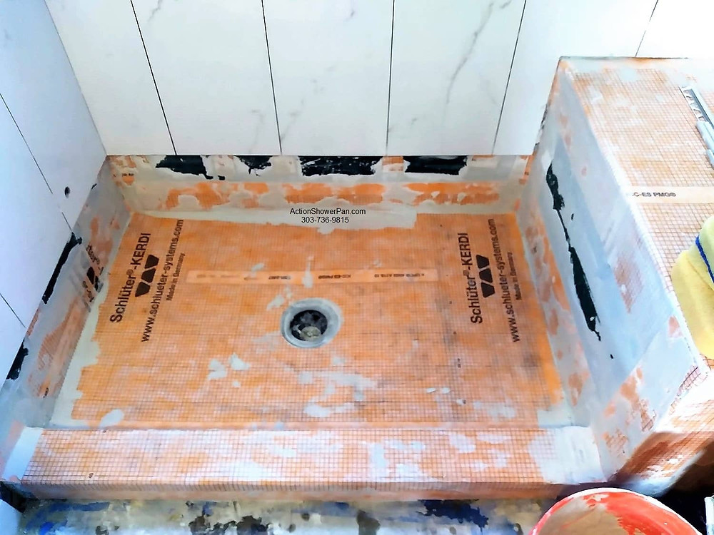 The shower pan installed is cement poured and waterproofed with Schluter-Kerdi membrane. The tile installation bonds directly to the membrane.