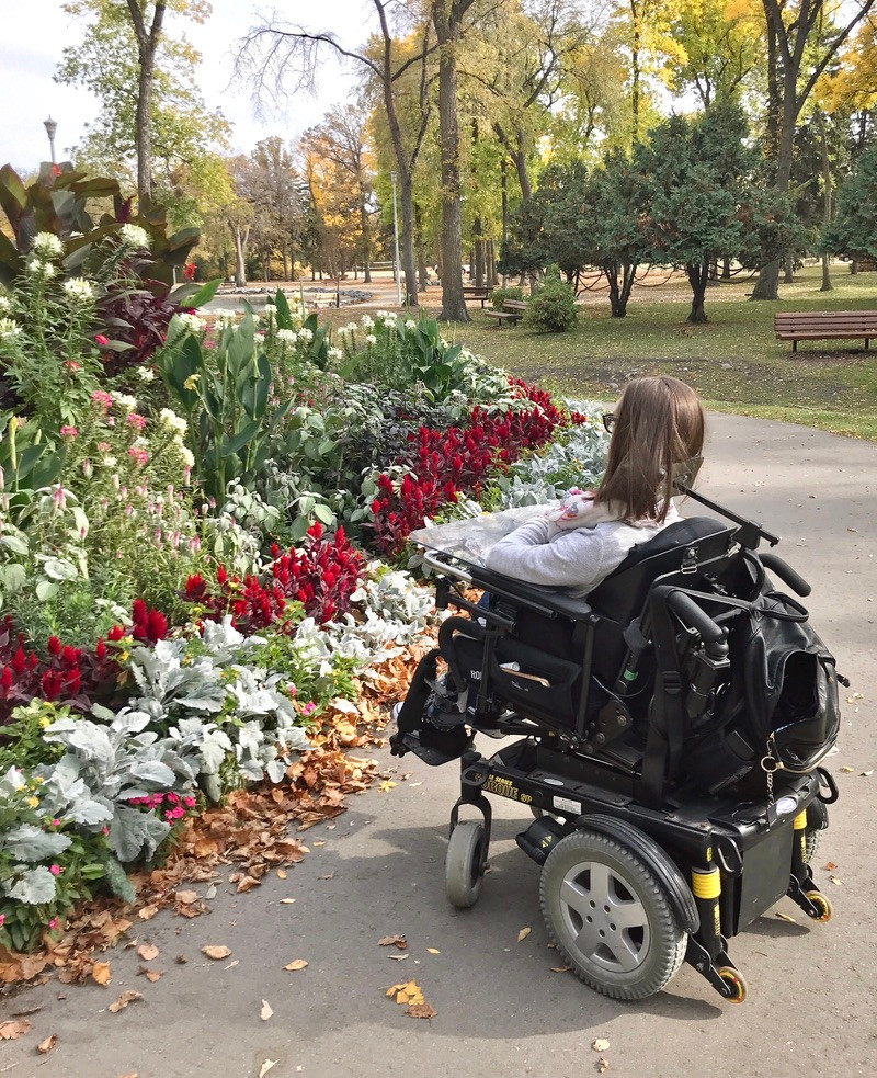 Cristina Waldner, a girl with SMA in wheelchair, looking at flowers at St. Vital Park in Winnipeg, Manitoba, Canada.