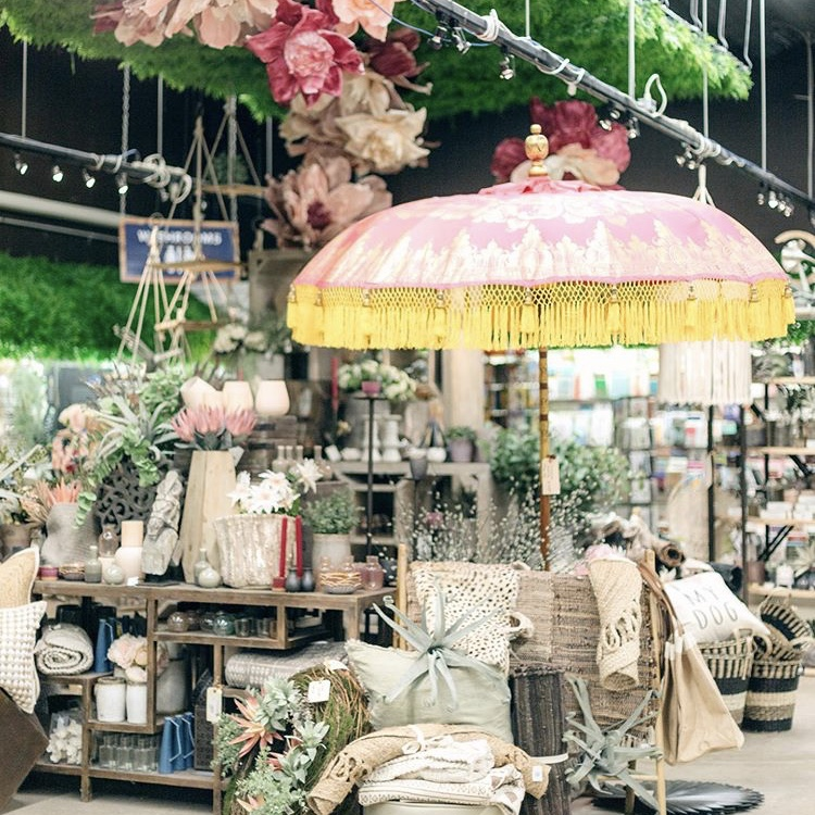 Shop display with tropical decor, a parasol, and a flower installation