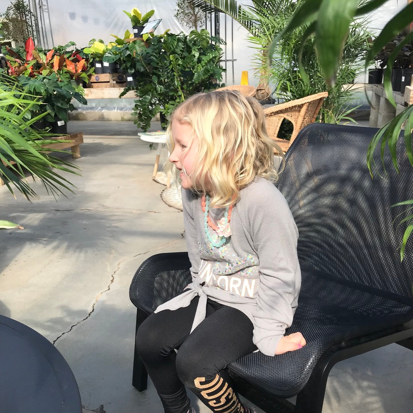 Little girl smiling while sitting on a chair in a greenhouse