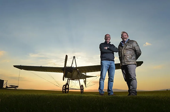 "A triumphant pose... but folks, it wasn't all that easy! UAS Pilot William McMinn (left), with TV presenter Dick Strawbridge after the flight in the Ferguson Flyer Replica for the BBC TV Series, ""The Great Flying Challenge""."