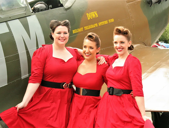 """Close harmony trio, The Swingtime Starlets pose beside the UAS """"Down"""" Spitfire at Castle Archdale"""