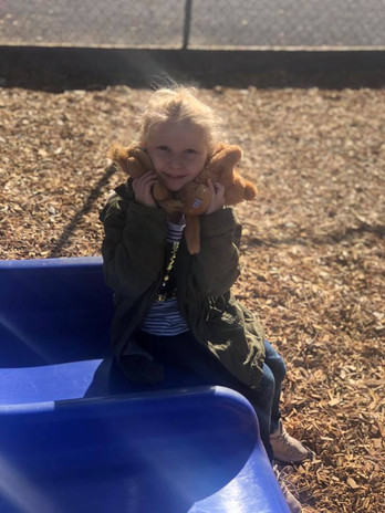 A girl smiles on a slide