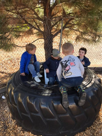 Boys playing on a large tire