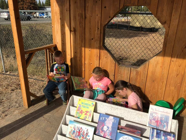 Children enjoying reading outdoors