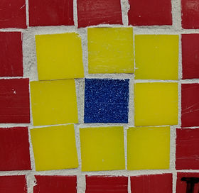 A mosaic with red, yellow, and blue tile.