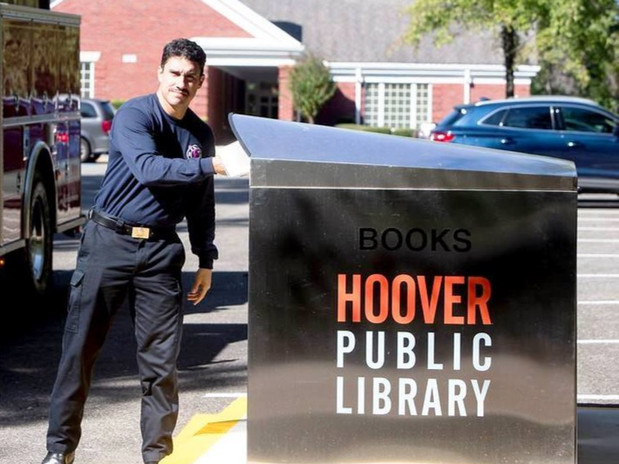 A book drop outside of the Hoover public library with a fireman returning a book.
