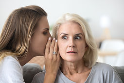 Shocked older woman listening to young f
