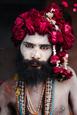 A holy man, covered in ash, looks into the camera and has a wreath of roses on his head.