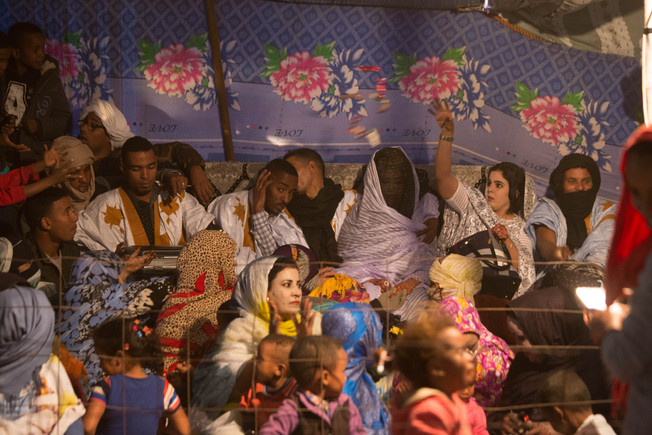 Weddings are one of the most important celebrations for sahrawis refugees. It is one of the few entertainments at the camp. The bride is leading a large gathering of women at the beginning of her wedding ceremony as the band (male) plays music.