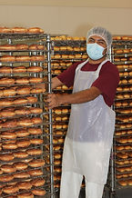 worker with rack of doughnuts