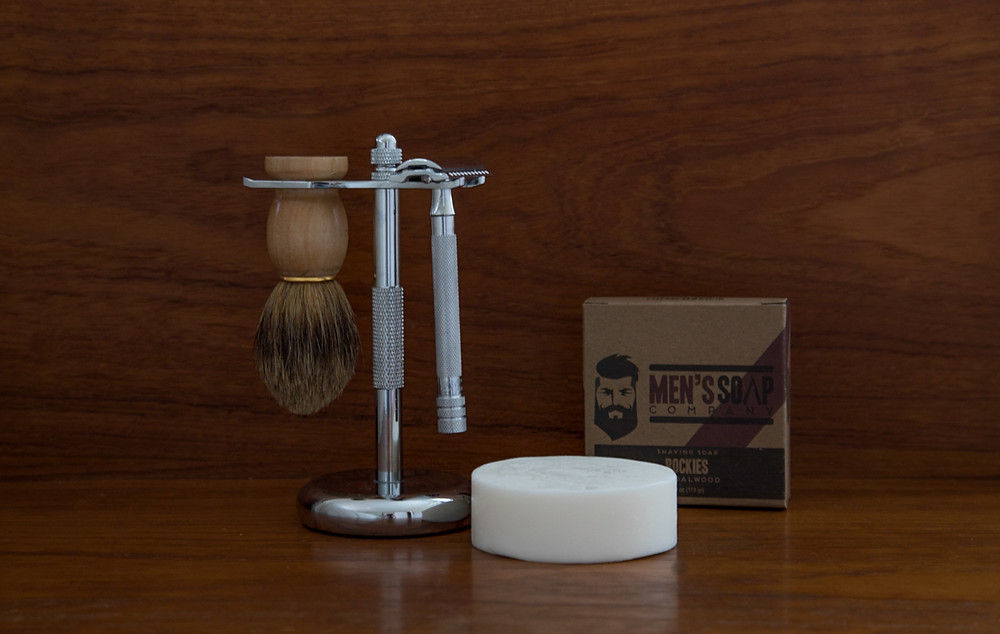An image of metal safety razor, sahve brush, stainless holder, and shave soap