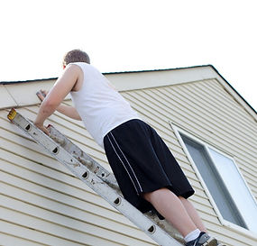 Student painters preparing house to be painted by scraping old paint