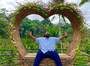 Jeff sitting on a bench made of sticks and shaped like a heart. There is a jungle in the background. Jeff is wearing blue jeans and a blue short sleeve button up shirt.