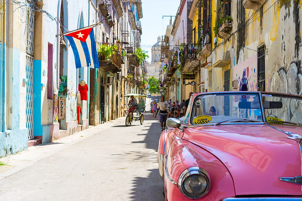 Photo of street in Havana. There is a bright pink convertible in the front right, people walking up the street and one man riding on a bicycle that has a top on it. A Cuban flag hangs from a building on the left, plants adorn window boxes, and the buildings are a little rough, old paint.
