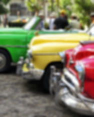 Antique cars lines up in a parkin lot. Red car in front, yellow in the middle, green in the back.