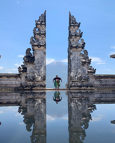 Jeff between two Balinese columns, which are reflected in the water.