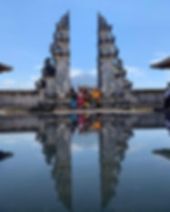 Group of travelers smiling and with their hands in the air. They are between two Balinese columns, which are reflected in the water.