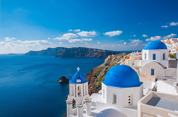 Photo of Santorini showing the ocean and cliffs in the background. In the foreground is the famous white church with blue rounded tops.