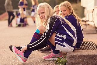 Portrait of Happy Girls Tying Shoes