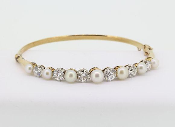 Natural pearl and diamond bangle.