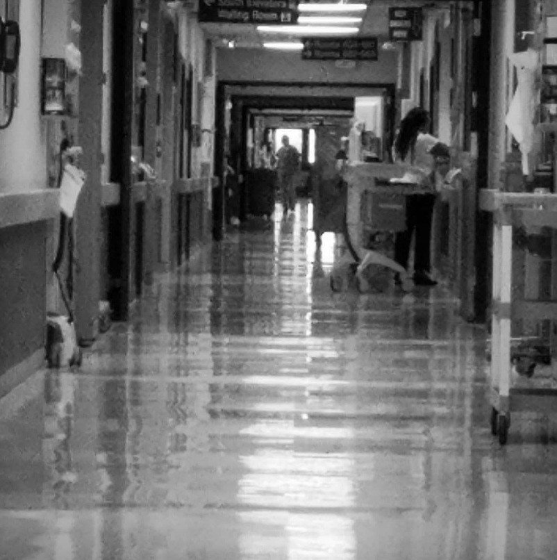 A photo I took from the end of the hall near my brother's hospital room. The nurse you see on the right is standing near his door. I blurred the image because that was how my life felt.