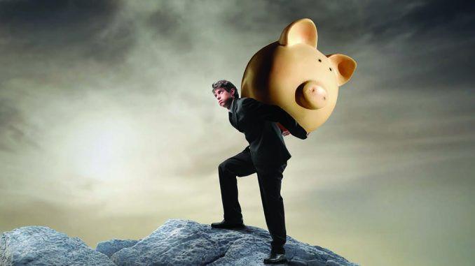 Young man hauling a piggy bank up a mountain