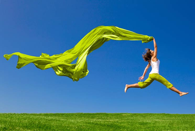 Woman leaping with joy in field