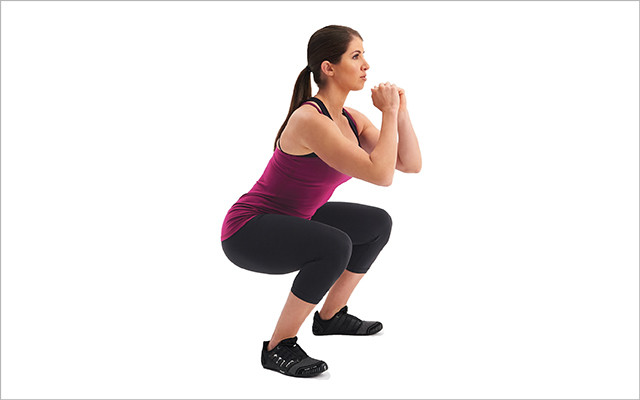 Real woman doing squats at the gym