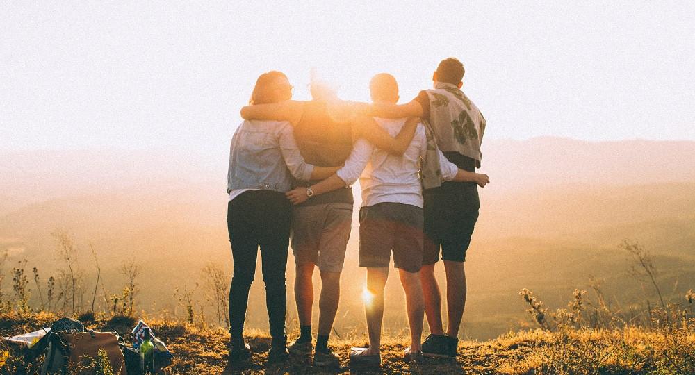 Gruppen von vier Leuten, die die Arme umeinander gelegt haben und den Sonnenuntergang ansehen.