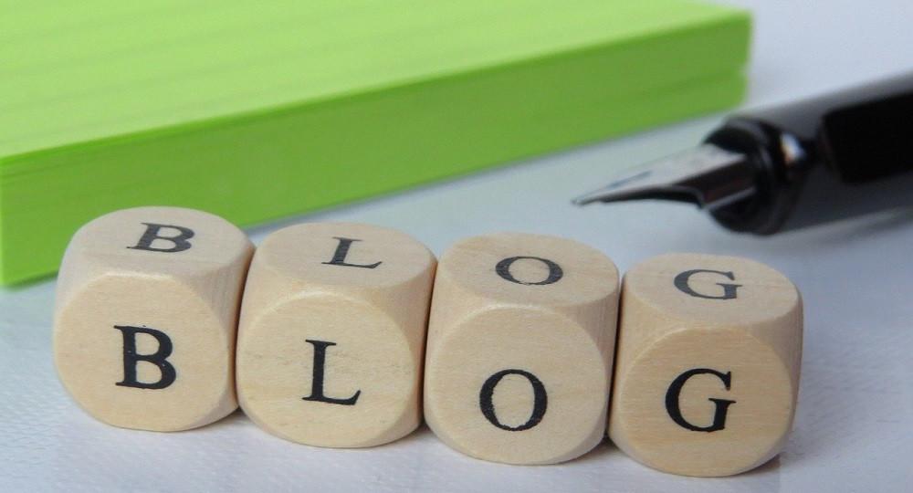 """4 Würfel mit Buchstaben bilden das Wort """"Blog"""". Ein Füller und ein grüner Papierblock sind im Hintergrund zu sehen."""
