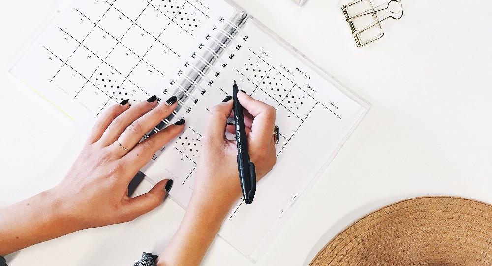 Frauenhände mit schwarzem Nagellack, schwarzer Stift in der rechten Hand, über einem aufgeschlagenem Terminkalender.