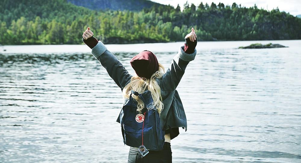 Blonde, langhaarige Frau mit Mütze und Rucksack, die vor Freude die Arme hoch reißt. Im Hintergrund sieht man einen See und Wald.
