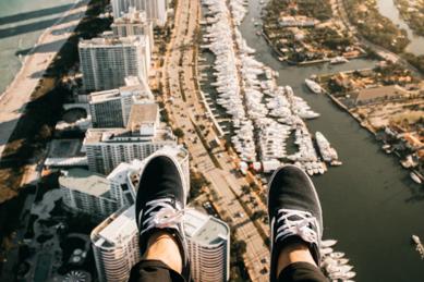 Füße im Vordergrund; im Hintergrund sieht man eine Stadt von oben