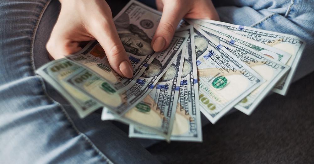 Frauenhände, die mehrere Geldscheine auffächern.