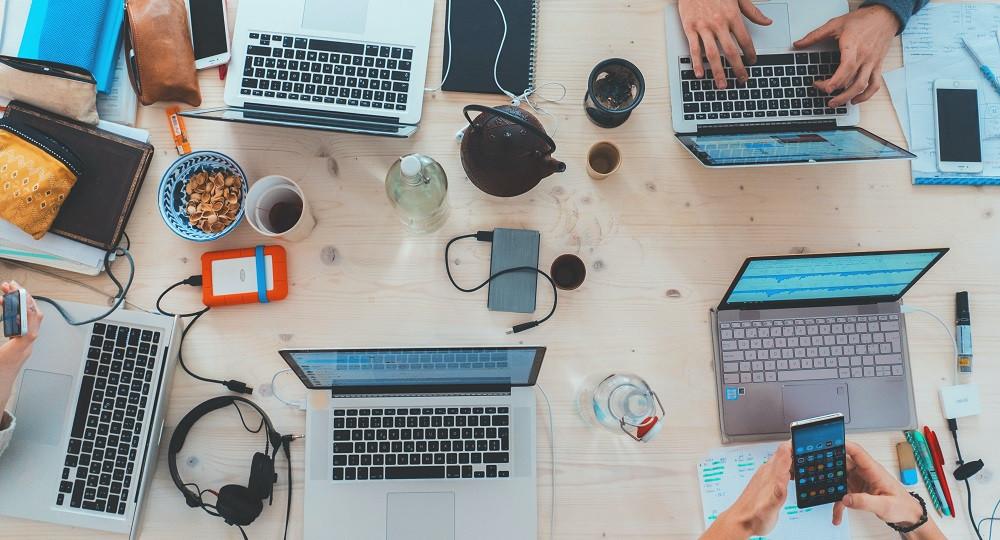 Tisch von oben mit mehreren Laptops, Handy und ähnliches.