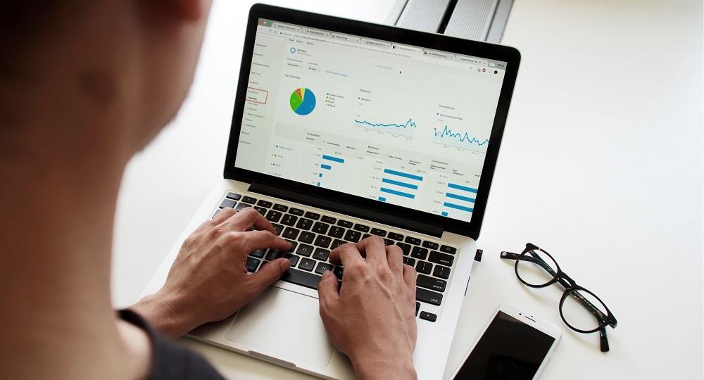 Mann am Laptop. Auf dem Laptop sieht man eine Datenauswertung in Form von Diagrammen.
