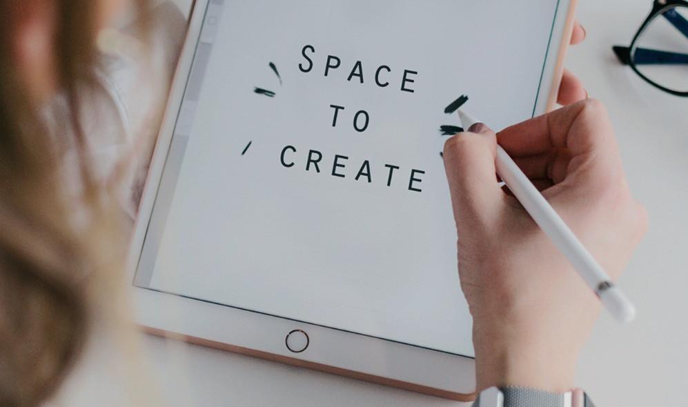 """Frau schreibt den Text """"Space to Create"""" auf ein iPad"""