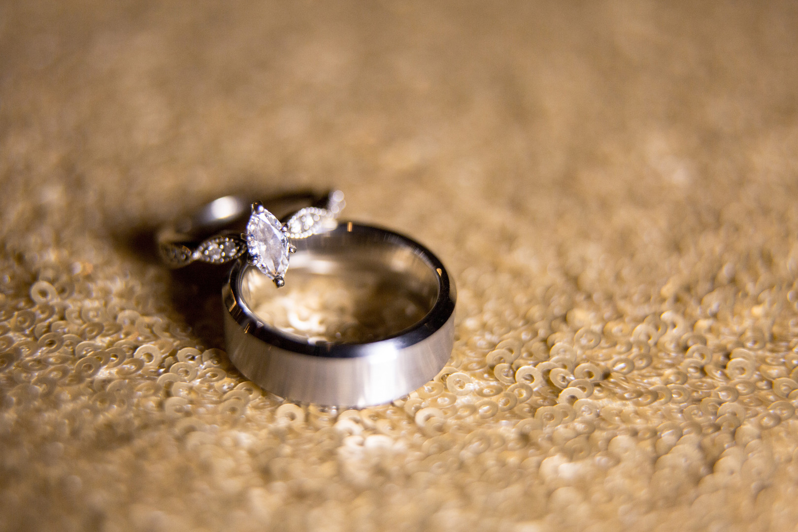macro ring shot of wedding rings with blurry sequin background