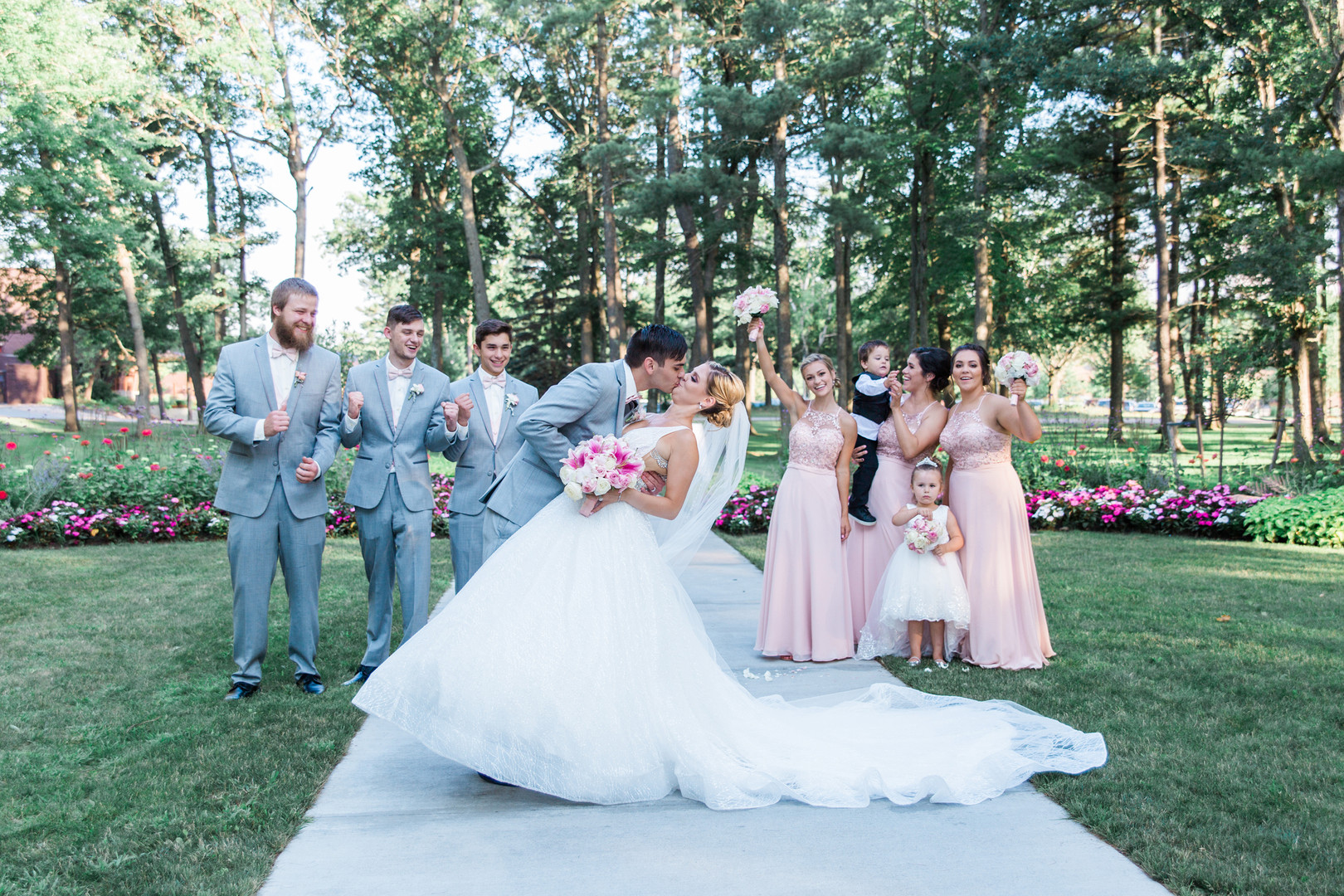 bride and groom dip for a kiss with bridal party cheering in background - fun bridal party pose
