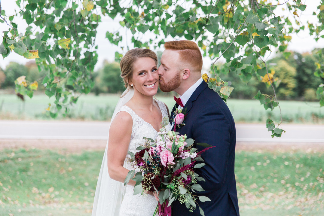 groom kissing brides cheek in front of green foilage tree